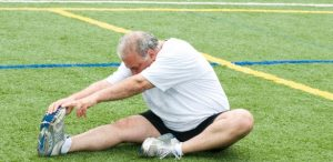 homem-meia-idade-faz-exercicio-ao-ar-livre-alongamento-grama-1375283423172_615x300